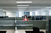 Lone woman in a cubicle among many empty office cubicles