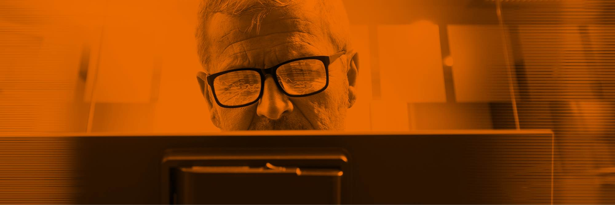 Man with glasses looking at analytics on computer screen
