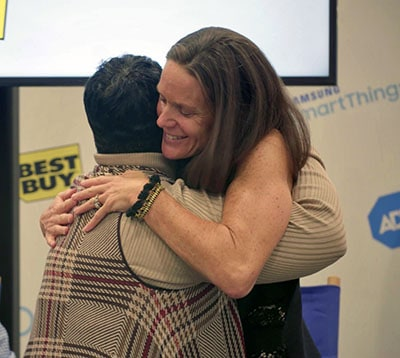 Lawton Carrescia gives the ADT dispatcher, Leatrice Johnson a hug.
