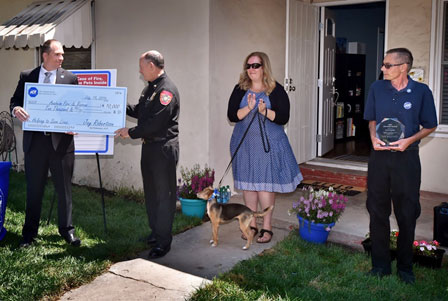 ADT vice president of marketing Jay Robertson presents a check for $10,000 to Anaheim Fire & Rescue's Deputy Chief Rusty Coffelt as  Amber Cooper, Fiona and Dave Tompkins look on.