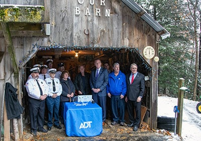 The Sunapee Fire Departmentn along with Barb & Jim Dulling pose in their barn with Tim McKinney, VP from ADT.