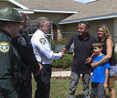 Terry France (with Colleen and Jacob) thanks Chief Reeser, Officer Tucker and Deputy Cohen outside the France home a month after the ordeal.