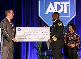 ADT CEO Tim Whall presents a check to Ft. Worth Fire Department Fire Chief Rudy Jackson