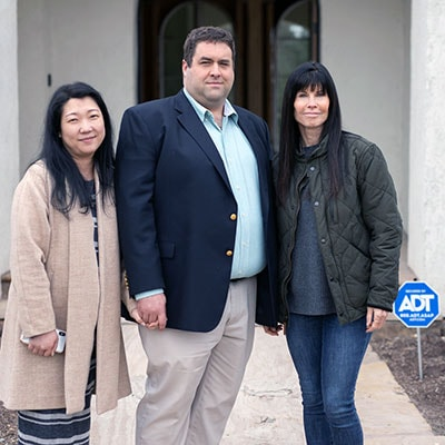 Bret and Ana Jensen with his mother Coleen stand outside their home in Spring TX