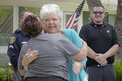 Suzanne Smith gives ADT Dispatcher Stacey Fioravanti a hug.