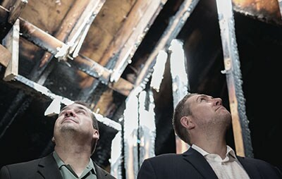 Rich Wagner and Nate Schnerch look at the fire damange done to their Winnipeg home.