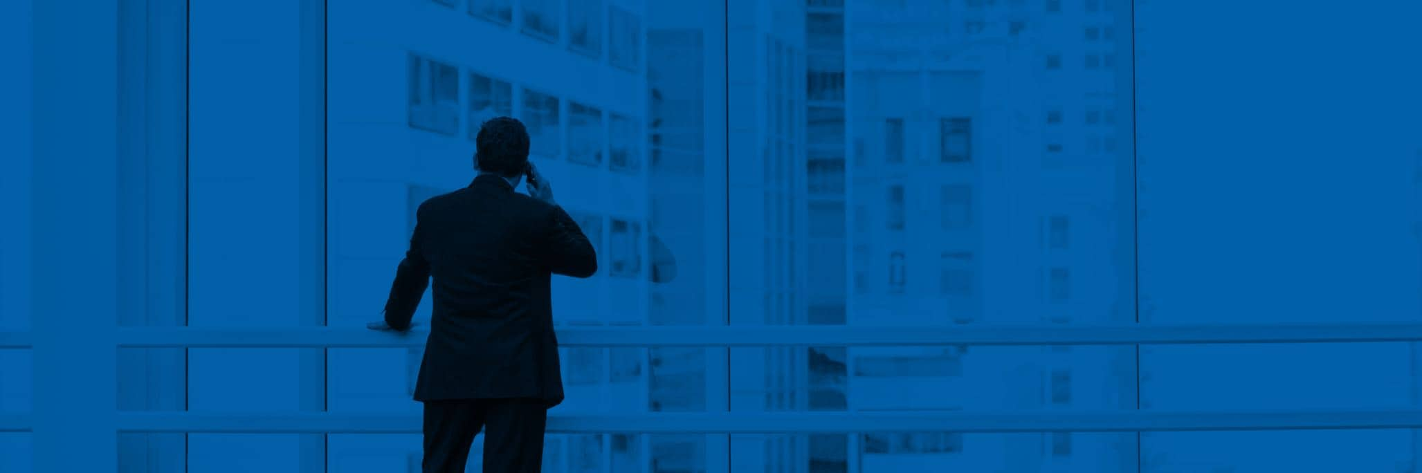 Man on phone looking out window in high-rise office building