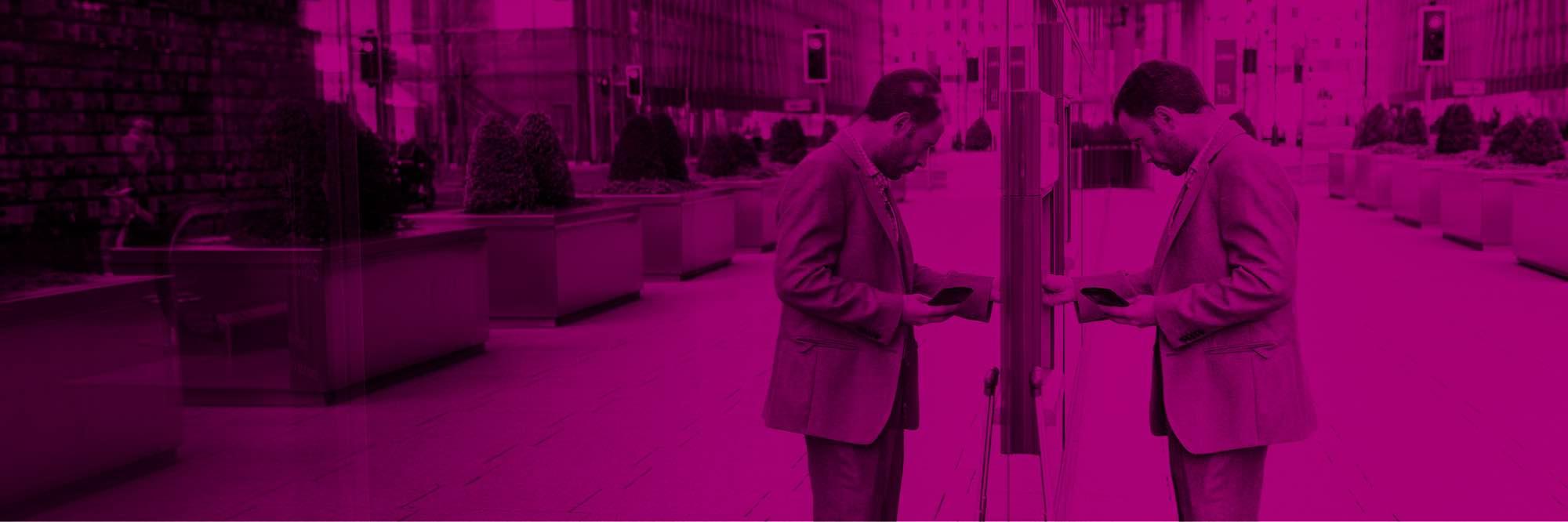 Man on city sidewalk using ATM machine