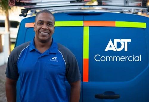 Smiling ADT Commercial technician at rear doors of ADT Commercial van